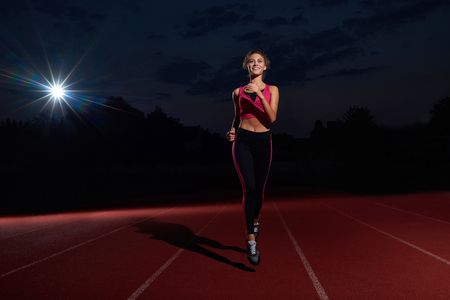 Foto de Positivity and happy young woman in sport wear running forward on track, looking and smiling at camera. Athletic girl with curly hair training, preparing alone to competition on stadium at night time. - Imagen libre de derechos