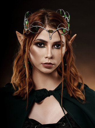Photo for Close up of fantasy and mystical elf with red hair and brown eyes wearing tiara with emeralds. Wonderful and charming woman in dark green cloak tied around her neck looking at camera. - Royalty Free Image