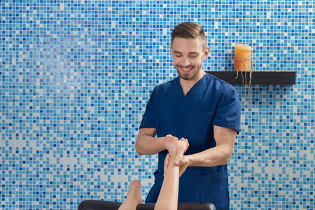 Front view of handsome male doctor in blue uniform smiling and talking while doing massage of feet in spa cosmetology salon. Masseur in process of working. Concept of treatment and care.