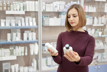 Foto de Pharmacy customer standing in drugstore and choosing medical products. Woman looking at cosmetic white bottles. Consumer buying treatment for health care. - Imagen libre de derechos