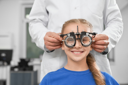 Photo for Ophthalmologist in white coat using special medical equipment for health of eyes, checking eyesight. Smiling girl sitting and looking at camera through test glasses. - Royalty Free Image