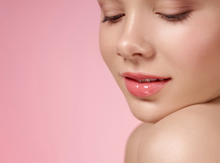 Photo pour Close up of well groomed face of young, cute model with pink, wet lips, natural make up on pink background. Beautiful female head leaning on bare shoulder. Concept of skin care. - image libre de droit