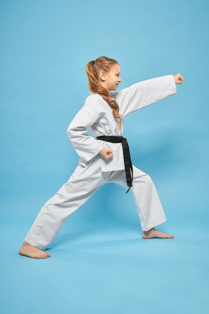 Foto de Side view of little strong girl in kimono standing in karate stance in studio. Pretty female teenager exercising and practising martial arts on blue isolated background. Concept of sport and judo. - Imagen libre de derechos