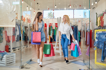 Photo pour Attractive smiling blonde and brunette coming out of clothing store in mall. Two friends with bags of purchases looking at each other, talking and laughing. Concept of good shopping. - image libre de droit