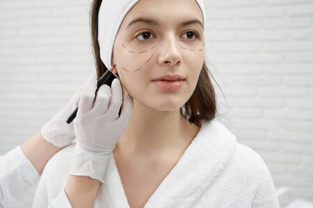 Front view of female adult sitting in beauty salon and looking forward while beautician doing markup on face before lifting on face. Young woman caring about skin and beauty. Concept of facials.