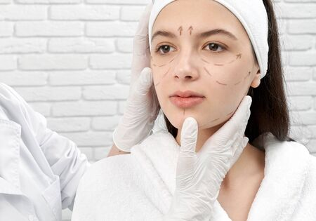 Front view of young female client looking forward while professional doctor examining skin before lifting. Pretty brunette with markup on face in salon. Concept of medical procedure.