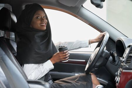 Photo for Cheerful african woman holding hand on steering wheel and coffee cup while driving car. Beautiful young muslim woman in black hijab sitting in car, looking at camera. - Royalty Free Image