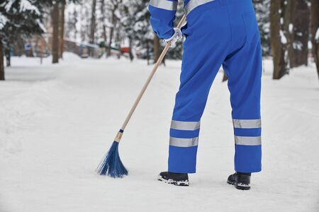 Photo pour Man cleaning snow with broom. Worker wearing in blue uniform with safety band holding plastic broom. Janior using tool for manual snow removal. Concept of city service. - image libre de droit