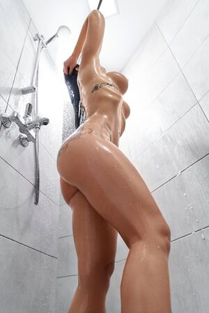 View from below of naked sexy woman with tattoos in process of taking shower at home. Seductive young model with hot sporty body washing long dark hair. Concept of erotica and passion.