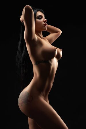 Photo for Gorgeous, hot brunette with perfect figure and tattoos posing with closed eyes. Sexy, passionate woman having naked, nude body, standing in studio on black isolated background. - Royalty Free Image