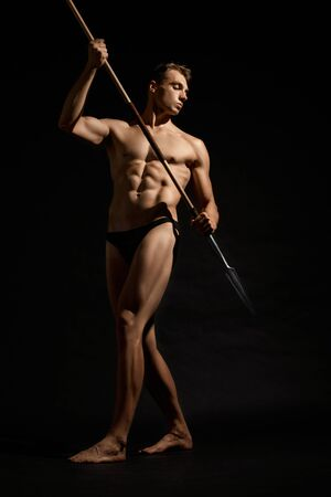 Photo pour Side view of young athletic warrior with perfect body holding spear. Handsome bodubuilder posing with cold weapon and looking away on black studio background. Concept of warrior, strength. - image libre de droit