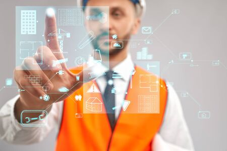 Photo pour Close up of architect wearing reflective vest and helmet. Selective focus of digital tactile charts screen, man touching virtual icon on projection. Concept of digitalization, construction. - image libre de droit