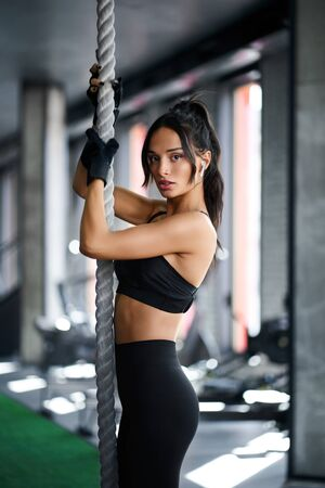 Side view of brunette slim woman posing in empty gym and holding white rope. Selective focus of pretty female with strong face training and looking at camera, fake grass on floor. Concept of sport.