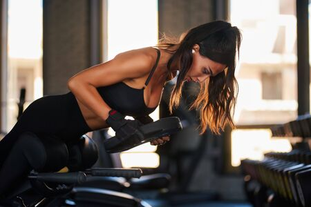 Photo pour Close up of young woman using wireless headpohnes, doing hyperextension with weighting at gym. Brunette slim female flexing back and abdominal muscles on bench, looking down. Concept of sport. - image libre de droit