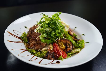 Photo pour Close up of tasty fresh warm salad with grilled meat, avocado, grilled vegetables and mushrooms and lettuce. Top view of healthy dish served with brown sauce on white plate in restaurant. - image libre de droit