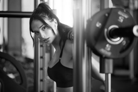 Photo for Side crop of brunette female bodybuilder using wireless headphones and doing squats in multipower smith machine, looking at camera. Srtong woman with slim body training legs in gym, black and white. - Royalty Free Image