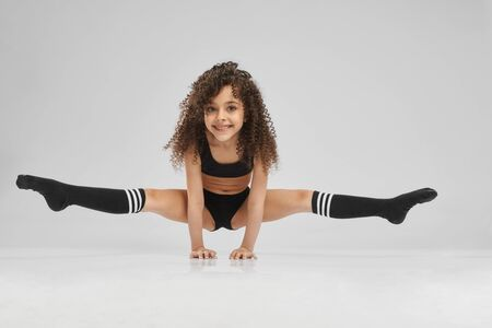 Photo pour Little female professional gymnast doing split, standing on arms on floor, isolated on gray studio background. Smiling girl in black sportswear and knee socks with curly hair showing flexibility. - image libre de droit