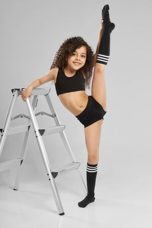 Photo pour Portrait of adorable smiling girl in black sportswear and knee socks demonstraiting split while standing, isolated on gray background. Little female gymnast showing flexibility, leaning on staircase. - image libre de droit