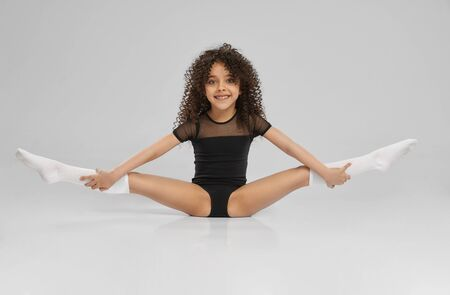 Photo pour Young female professional gymnast sitting on floor with legs wide up, isolated on gray studio background. Smiling girl in black sportswear and knee socks with curly hair showing flexibility. - image libre de droit