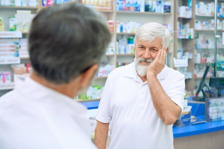 Photo pour Selective focus of senior man with tooth ache consulting with pharmacist. Back view of unrecognizable man in white uniform offering medicineswhile eldery male customer frowning painfully. - image libre de droit