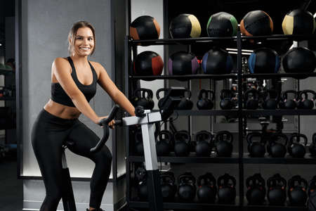 Foto für Smiling beautiful young woman in black sportswear engaged on exercise bike. Concept of active lifestyle and pump up body. - Lizenzfreies Bild