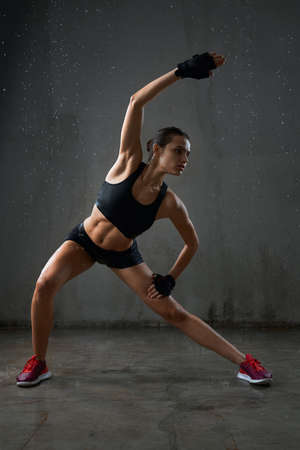 Photo pour Fit female model practicing side body incline in side squat pose before training, isolated on loft gray studio background. Portrait of wet muscular fitnesswoman posing in sports underwear under rain. - image libre de droit