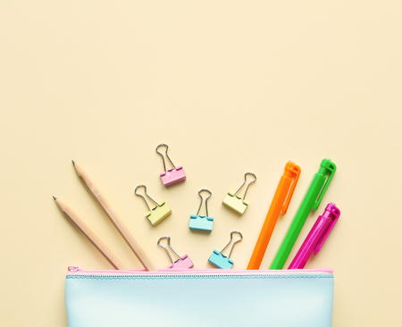 Photo pour Flat lay composition of pastel blue pencil case with pens, pencils,paper binders.Copy space,beige background.Top view on various stationery on desk. Creative workspace background.Back to school concept. - image libre de droit