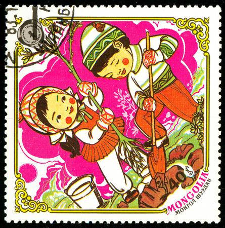 Ukraine - circa 2018: A postage stamp printed in Mongolia show Children plant a tree. Series: 10 years Children Fund, Happy childhood. Circa 1983.