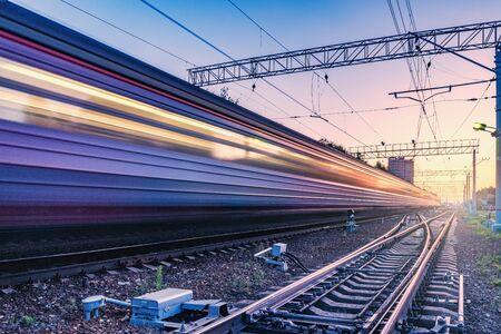 Photo pour Passenger train moves fast at sunset time. - image libre de droit