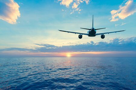 Flying of the passenger plane above the sea surface at sunset time.