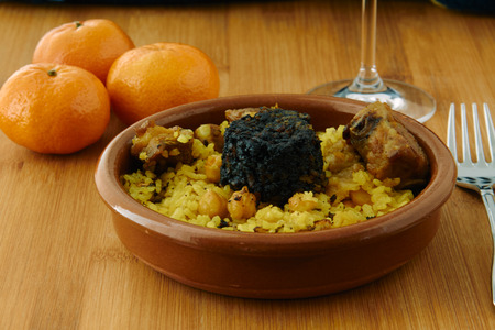 Photo pour Baked rice in a pottery dish accompanied by pork, chickpeas, blood sausage, tomato and garlic. Traditional arroz al horno from the area of Valencia, Spain - image libre de droit