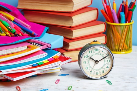 Foto de Composition lined with colorful school stationery. At 10 o'clock hour is time to study. Group of school supplies and books on wooden table - Imagen libre de derechos