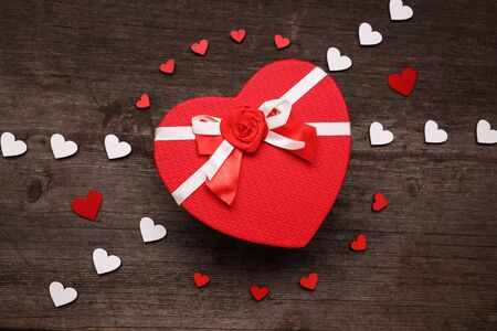 Photo pour The cover of the box in the shape of a heart. Composition with red and white hearts on a wooden background. Valentines day concept with hearts and gift box. Top view - image libre de droit
