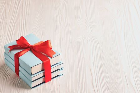 Foto de Books tied with ribbon on a wooden background with copy space: concept of donating books. - Imagen libre de derechos