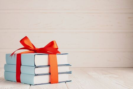 Foto de A stack of three books tied with a red ribbon with a bow and copy space: the concept of a good book - a good gift. - Imagen libre de derechos