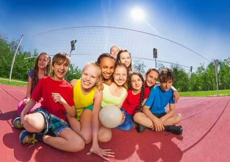 Happy funny teenagers sitting on volleyball court holding ball during summer sunny day