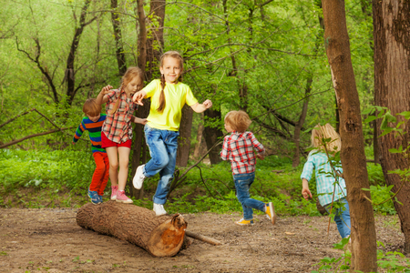 Portrait of cute little kids playing on a log, walking, jumping and balancing in the forest