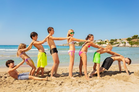 Happy friends playing beach games in summer