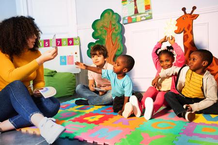 Foto de Many kids in kindergarten play games with teacher - Imagen libre de derechos