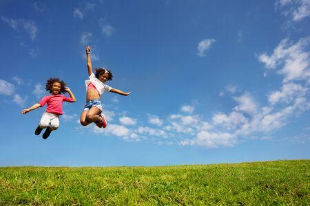 Photo pour Two happy girls jump high over blue sky on lawn - image libre de droit