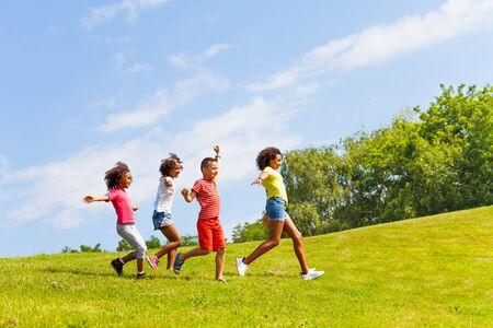 Foto de Side view of running kids group in the park lawn - Imagen libre de derechos