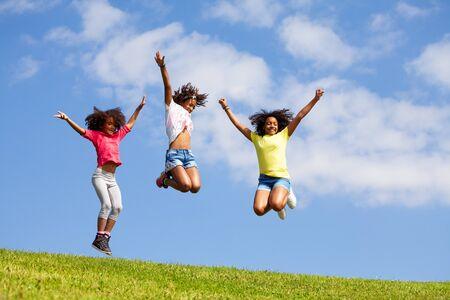 Photo pour Group three jumping girls over clean blue sky - image libre de droit