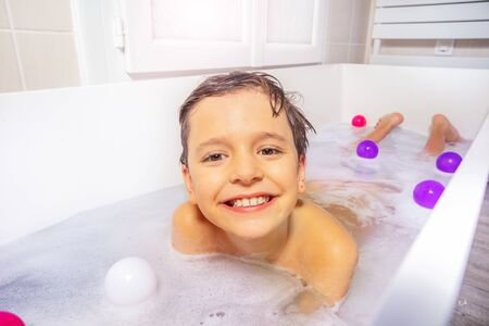 Photo pour Portrait of a boy play with toys and soap on the belly in the bath water at home - image libre de droit
