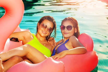 Photo for Two happy teens girls swim laying on the rose buoy in the swimming pool wearing sunglasses - Royalty Free Image
