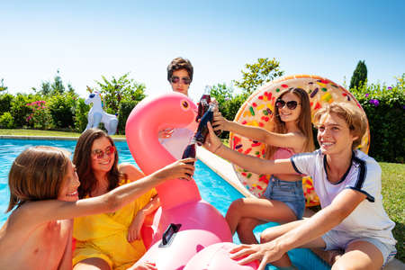 Photo for Group of teenage kids play chat and drink soda celebrating sitting on the border pool with inflatable buoys - Royalty Free Image
