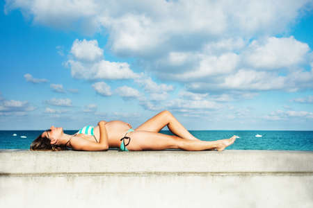 Photo pour Profile photo of a pregnant woman lay on the border of the pool holding belly, view over sky - image libre de droit