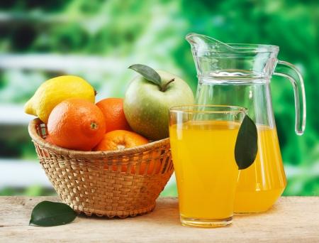 Foto de variety of fruit and juice on a wooden table in the garden - Imagen libre de derechos