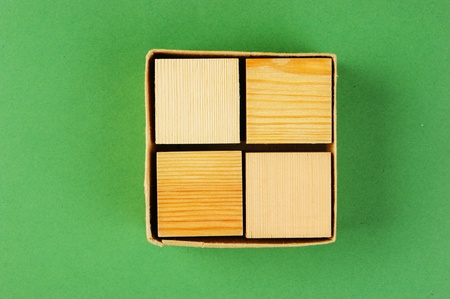 wooden geometric cube in a box on a green background