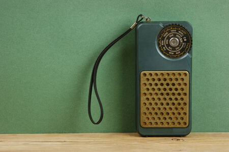 old radio on a wooden shelf in the green wall