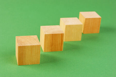 wooden geometric cube on a green background